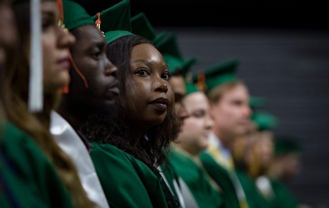 A graduate listens as Kirk Cousins delivers his keynote address during the 2019 spring convocation at Michigan State University, Friday, May 3, 2019, at the Breslin Center in East Lansing.