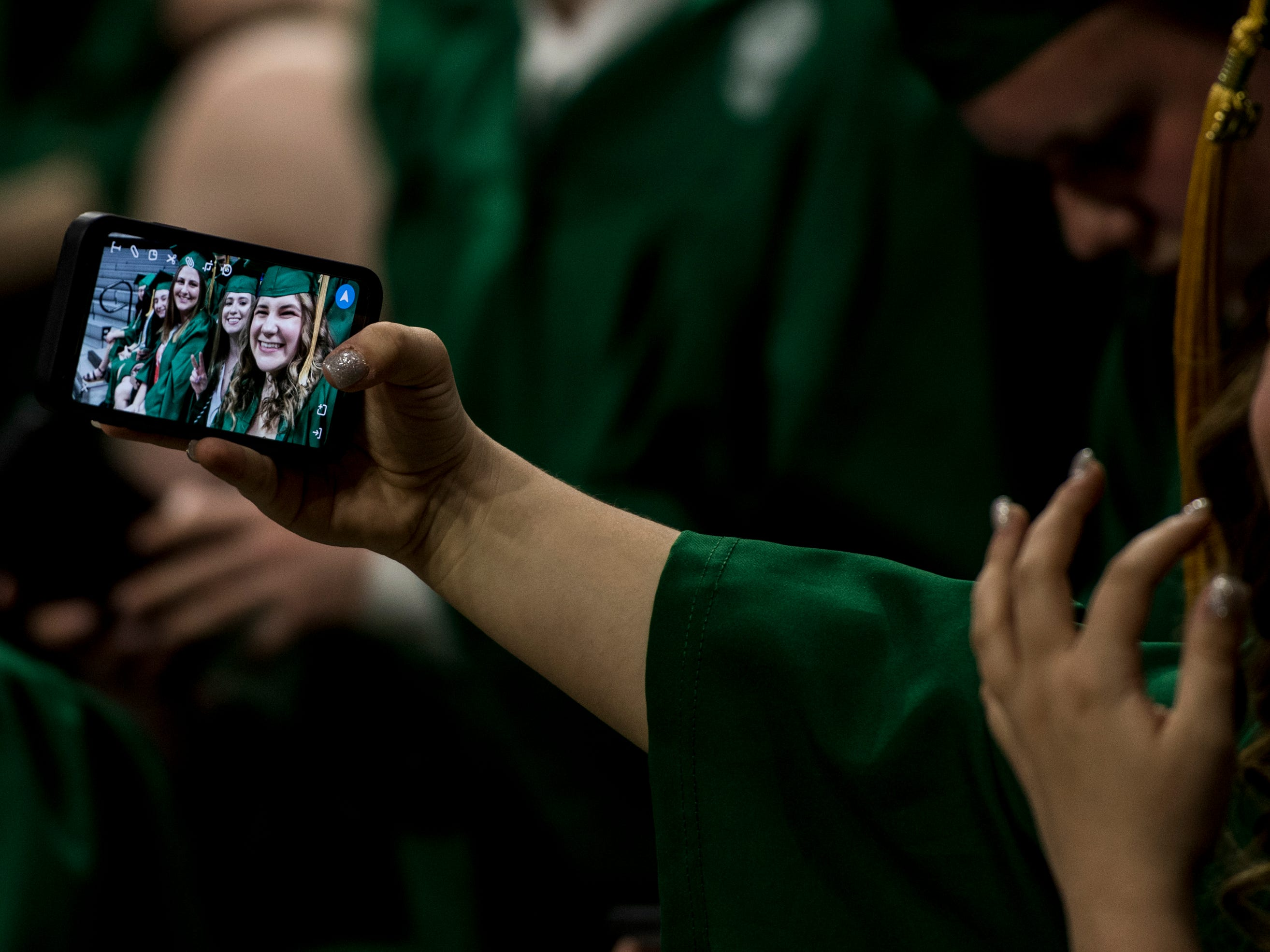 Michigan State University graduate Grace Medlin of Shelby Township laughs after taking a selfie during commencement, Friday, May 3, 2019, at the Breslin Center in East Lansing.