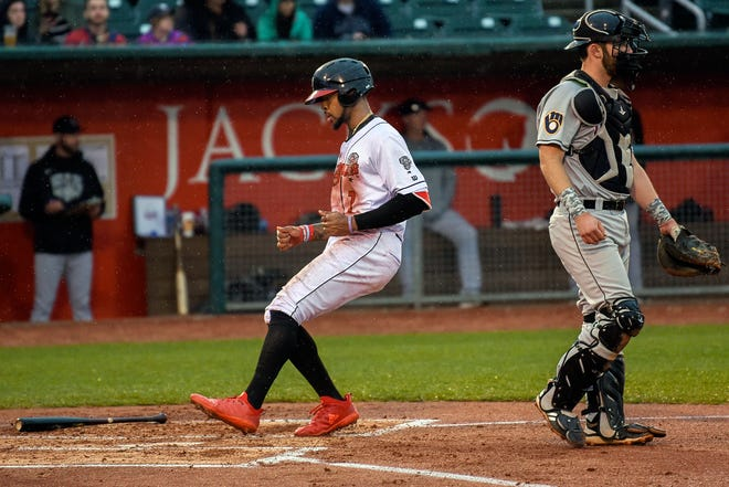 Lugnuts right fielder DJ Neal, left, scores a run in the second inning during Lansing's game against the Wisconsin Timber Rattlers on Thursday, May 2, 2019, at Cooley Law School Stadium in Lansing.