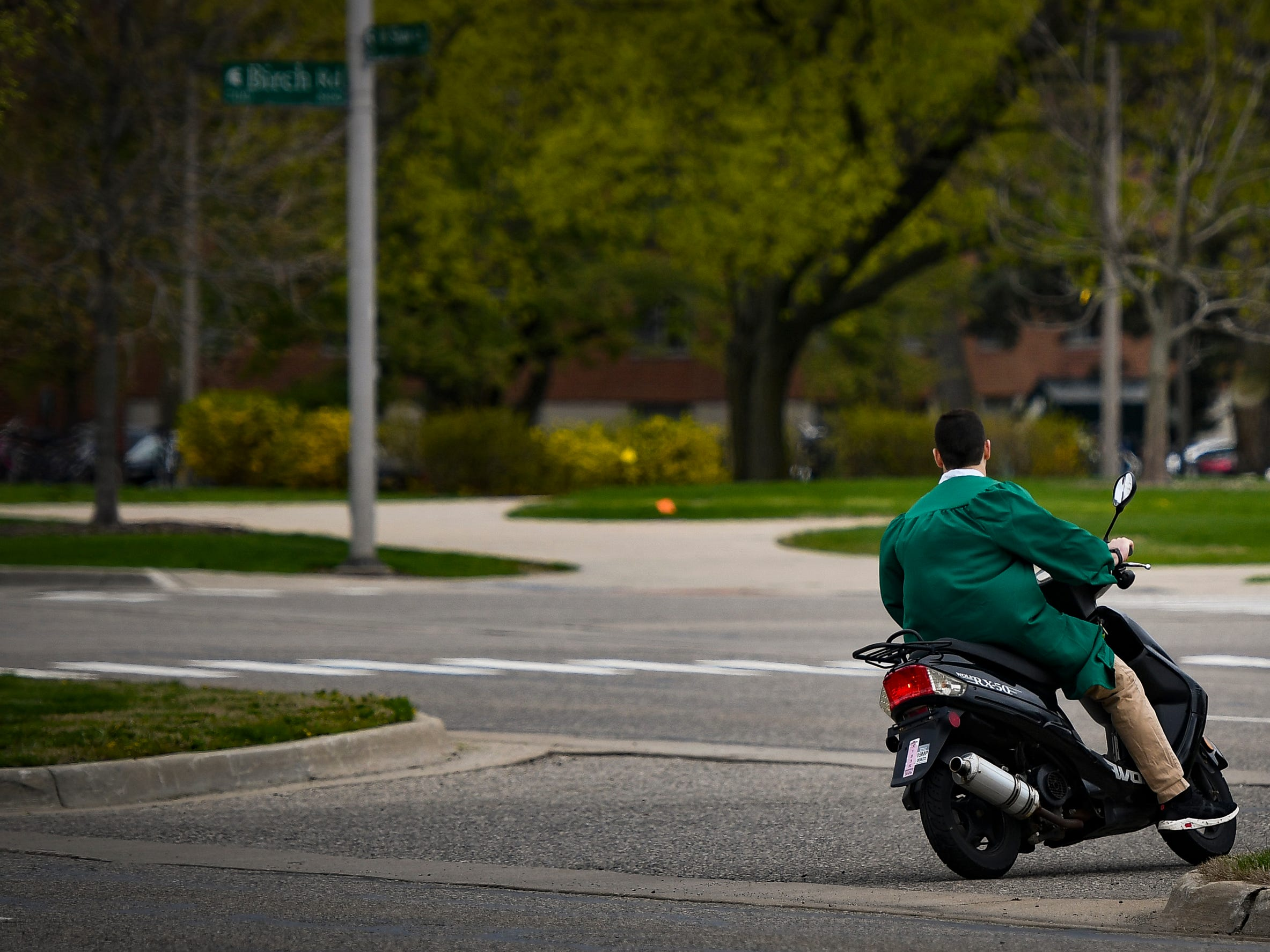 An MSU graduate leaves the Breslin Center via moped Friday, May 3, 2019, following the 2019 commencement.