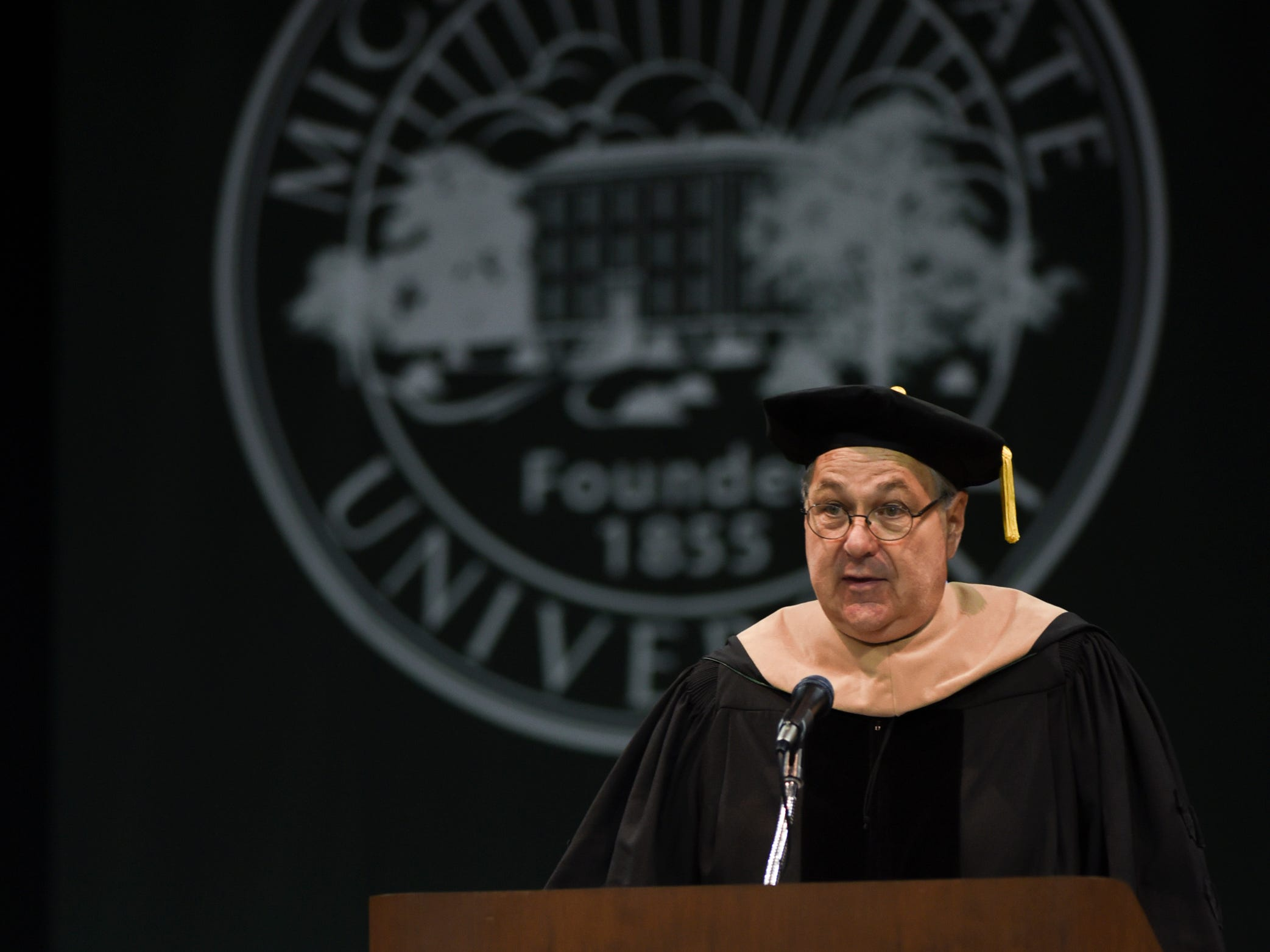 Bill Demmer, CEO of Demmer Holdings Inc., addresses Michigan State University graduates Friday, May 3, 2019, during commencement.  Demmer received an honorary degree of Doctor of Business from MSU.
