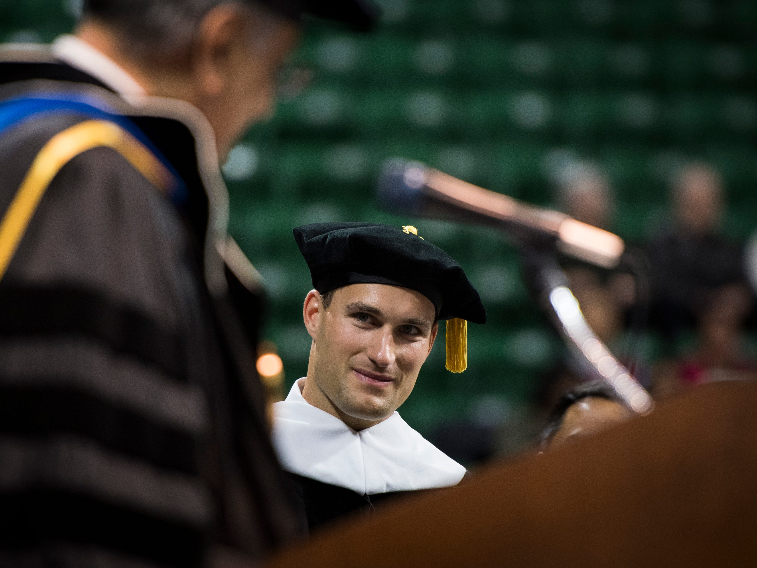 """""""Only a select few reach the epitome of their sport, but your work ethic, combined with the support of your family and your deep faith helped you reach your goals,"""" Michigan State University acting President Satish Udpa, left, said, introducing former MSU quarterback and NFL player Kirk Cousins, Friday, May 3, 2019, during spring convocation at Breslin Center in East Lansing, Michigan. Cousins was presented an honorary doctorate of humanities."""