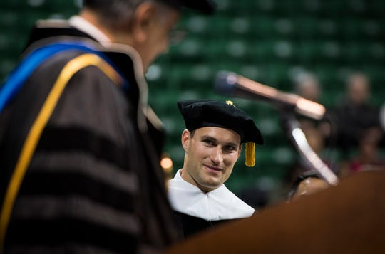 """Only a select few reach the epitome of their sport, but your work ethic, combined with the support of your family and your deep faith helped you reach your goals,"" Michigan State University acting President Satish Udpa, left, said, introducing former MSU quarterback and NFL player Kirk Cousins, Friday, May 3, 2019, during spring convocation at Breslin Center in East Lansing, Michigan. Cousins was presented an honorary doctorate of humanities."