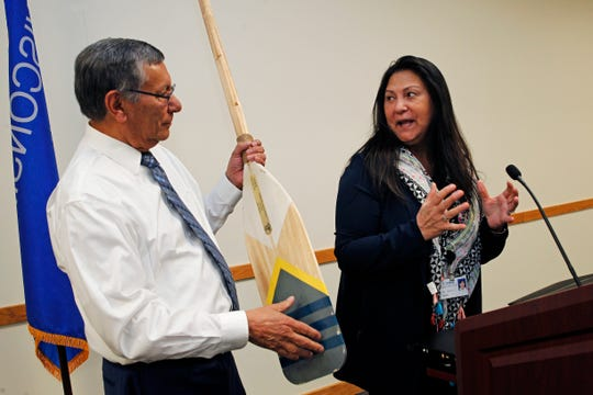 UMOS President and CEO Lupe Martinez holds one of two engraved paddles presented to him by Tina Koehn on behalf of his staff on Friday to recognize his many years of service to UMOS.