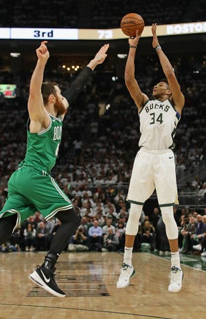 Giannis Antetokounmpo shoots a three-point shot over Aron Baynes of the Boston Celtics at Fiserv Forum on April 30.