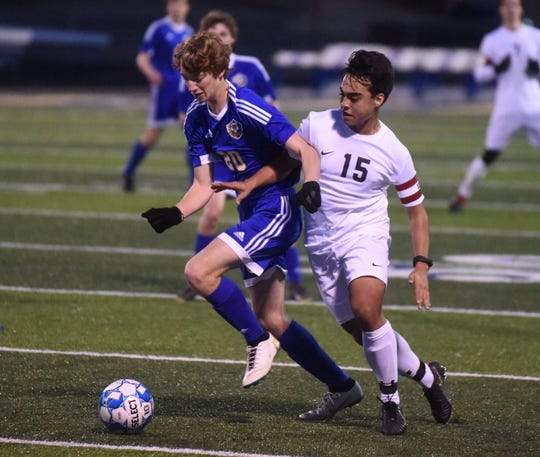 Mountain Home's Joseph Spurlin (20) battles  a Searcy player during their match earlier this season at Bomber Stadium. The Bombers edged the Lions in a shootout Thursday night at Searcy to clinch the 5A-East Conference title.