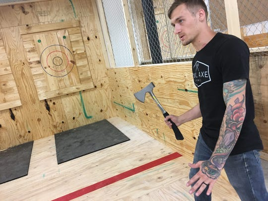 Manager Brendan Messex talks to a customer at Civil Axe Throwing in Montgomery.