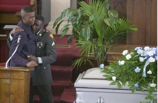 Fishoe's son's Zenas Fishoe and Anthony James Lacy embrace each other at the funeral of their father.