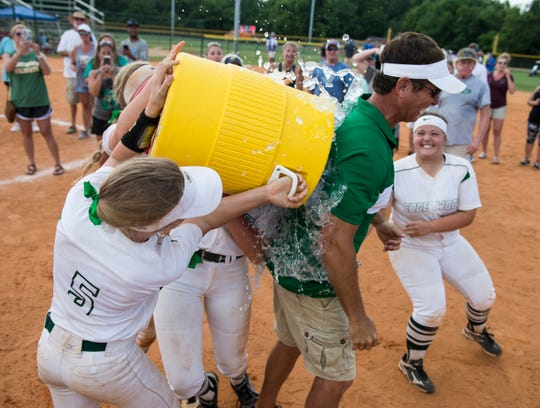 Edgewood head coach Mark Segrest gets a water cooler bath after winning the AISA Class AA softball championship tournament at Lagoon Park in Montgomery, Ala., on Friday, May 3, 2019.  Edgewood defeated South Choctaw 7-0.