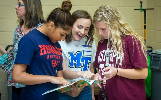 Aysha Dean, Melody Kinney and Ainsley Vendur look at their first grade yearbook as they joined other former students at Discovery School at Bellwood in the Senior Walk Friday, May 3, 2019.