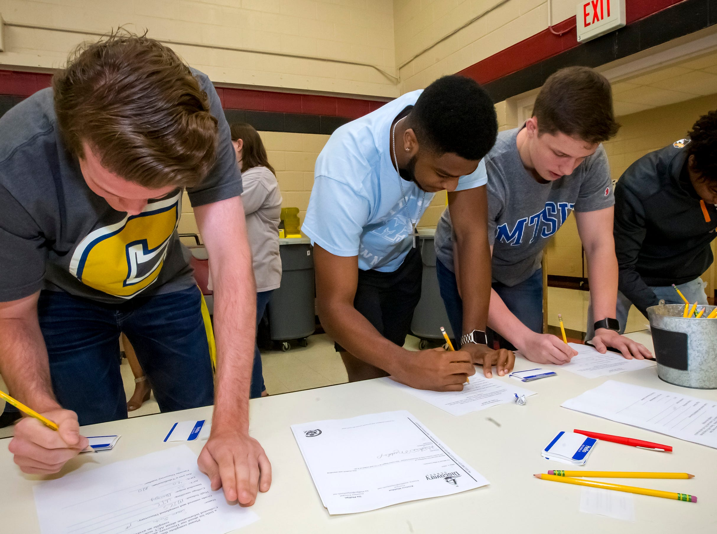 Sam Smith, Joesph Howard, Andrew Bruce and Evan Alford sign in as they joined other former students at Discovery School at Bellwood in the Senior Walk Friday, May 3, 2019.