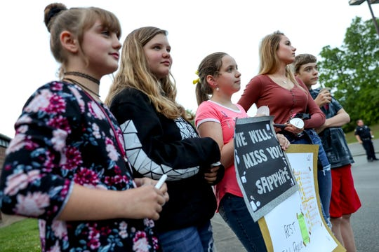 From left to right: Mina Barton, 11, Marisa Clifford, 12, Tru Fowler, 11, Jade Williams, 17, and Brennen Fowler, 12 — all friends of Sapphire McGlothlin-Pee — stand in the back of the crowd with a sign they made for their slain friend at Westmoreland Middle School in Westmoreland, Tenn., on Thursday, May 2, 2019. The friends joined a vigil held for the seven victims of a slaying over the weekend in Sumner County.