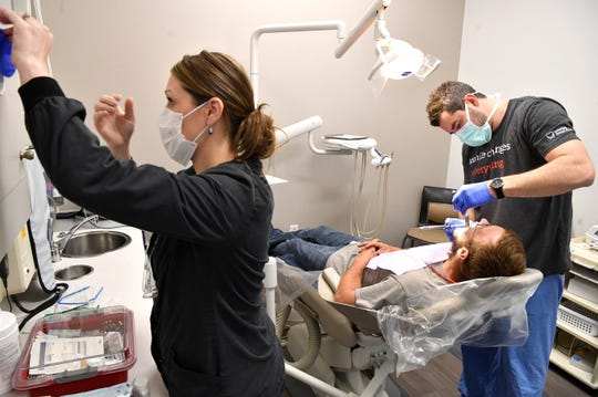 Jen Matlock does the prep work as dentist Daniel Coke prepares to remove a tooth from Brian Savage, who came into Interfaith Dental, with an emergency situation on Thursday.