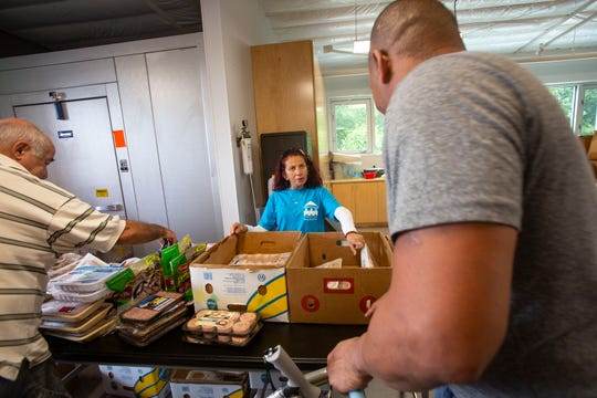 Grace Place Food Pantry manager Patty Urrutia, center, helps with food distribution, Friday, May, 3, 2019, at Grace Place Food Pantry in Golden Gate.