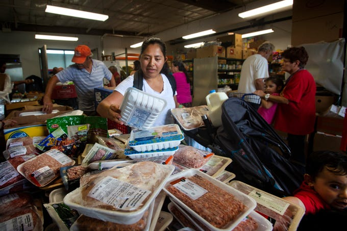 Veronica Roblero, of Golden Gate, picks up groceries, with her son Alejandro Estrada, 1, at lower right, Friday, May, 3, 2019, at Grace Place Food Pantry in Golden Gate.
