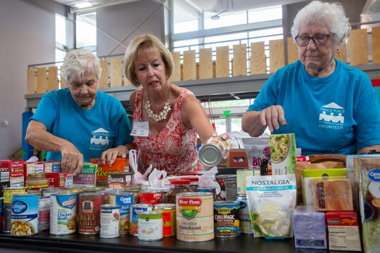 Volunteers, from left, Barbara Lavdano, of Naples, Pat Bosscher, a Naples seasonal resident from Northville, Michigan, and Helga Schoennagel of Golden Gate, restock a table with canned goods, Friday, May, 3, 2019, at Grace Place Food Pantry in Golden Gate.