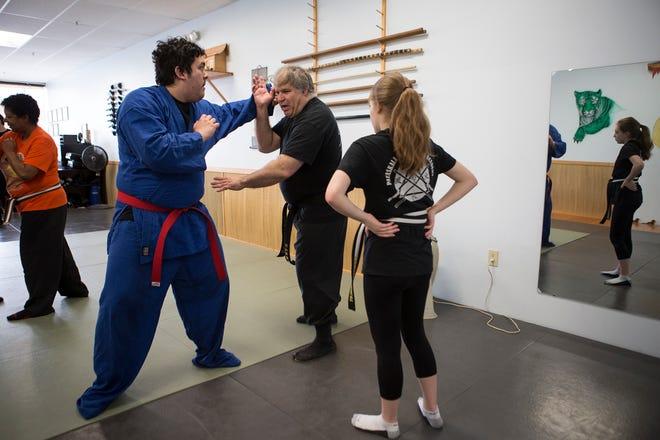 Chuck Jackson, (center) owner of Pataskala Martial Arts Academy democrats a move to students.