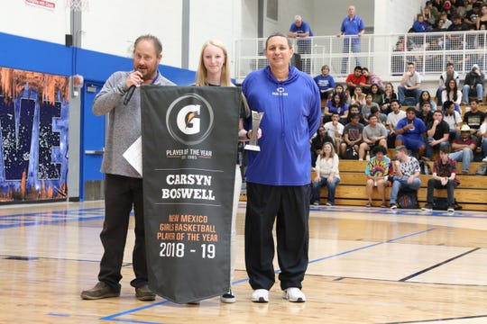 Carsyn Boswell is surrounded by CHS AD James Johns, left, and Cavegirls head coach John Zumbrun, right. Boswell was given her Gatorade Player of the Year banner on Friday at CHS' pep rally. She is the first Cavegirl to receive this honor.
