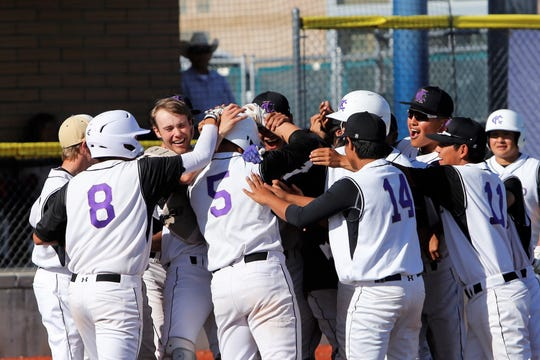 Kirtland Central players swarm Cadan Flack (5) after he hit a two-run home run against Bloomfield during Thursday's District 1-4A game at John Gutierrez Field in Bloomfield.