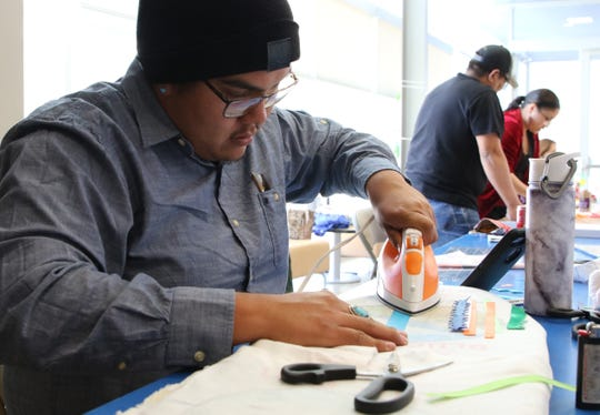 Darrell Yazzie Jr. irons a ribbon for the tobacco pouch he was making on Friday at Diné College's south campus in Shiprock.