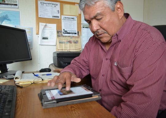 Gerald Moore, coordinating extension agent for the Navajo Nation with the University of Arizona, demonstrates how to use the website on Monday at his office in Window Rock, Ariz.