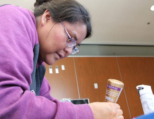Philmena Howard uses fabric glue to fasten together material for the tobacco pouch she was making on Friday at Diné College's south campus.
