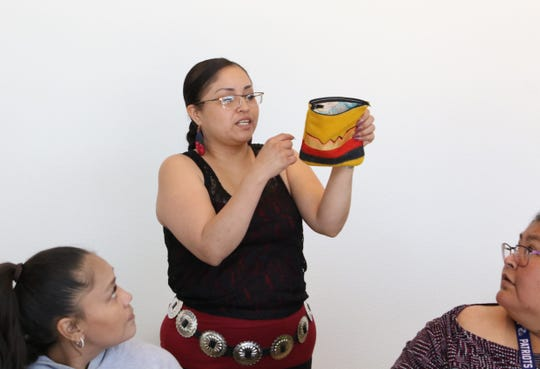 Workshop instructor Andrea Sekayumptewa, center, shows a tobacco pouch made during the Navajo Cultural Arts Program class on Friday at Diné College's south campus in Shiprock.