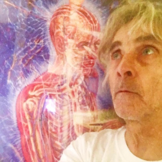 Art Kunkin's  friend, Ted Quinn, stands in front of an Alex Grey painting used by Art to illustrate the experience he had of  light shining through his own eyes.