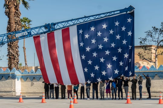 Volunteers came forward to hold the 30 by 36-foot American flag off the ground as Whites Steel's crane was raising it.