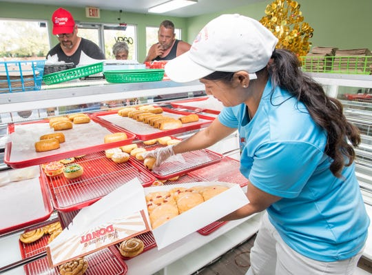Owner Chanthy Moeun fills a box with doughnuts at the new Breeze Donuts in Gulf Breeze on Friday.