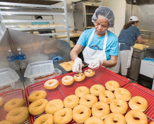 Thuok Pel adds bacon to maple bacon doughnuts at the new Breeze Donuts in Gulf Breeze on Friday.