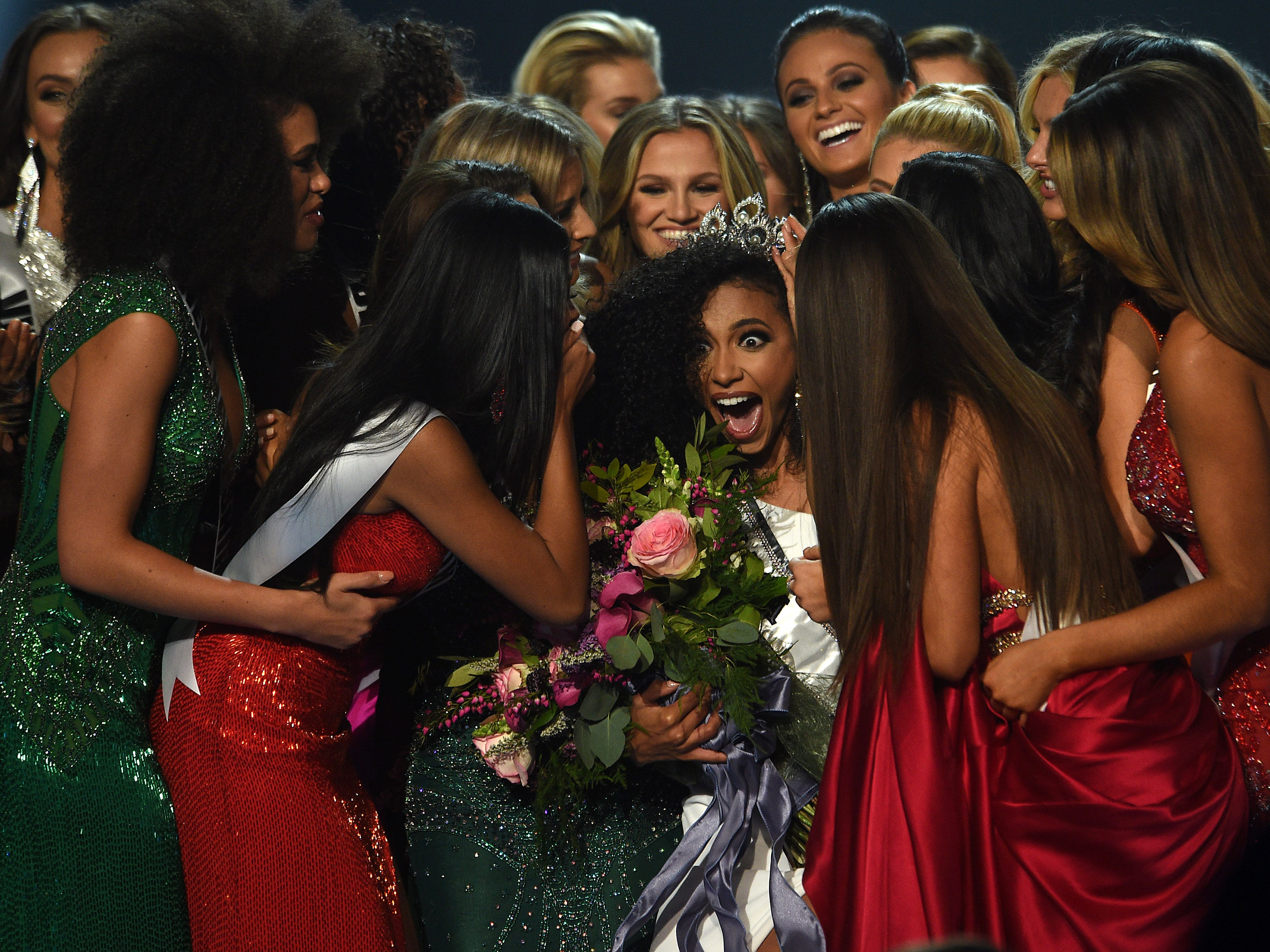 Miss North Carolina Cheslie Kryst, middle, gets mobbed by her fellow contestants after winning the 2019 Miss USA final competition in the Grand Theatre in the Grand Sierra Resort in Reno on May 2, 2019.