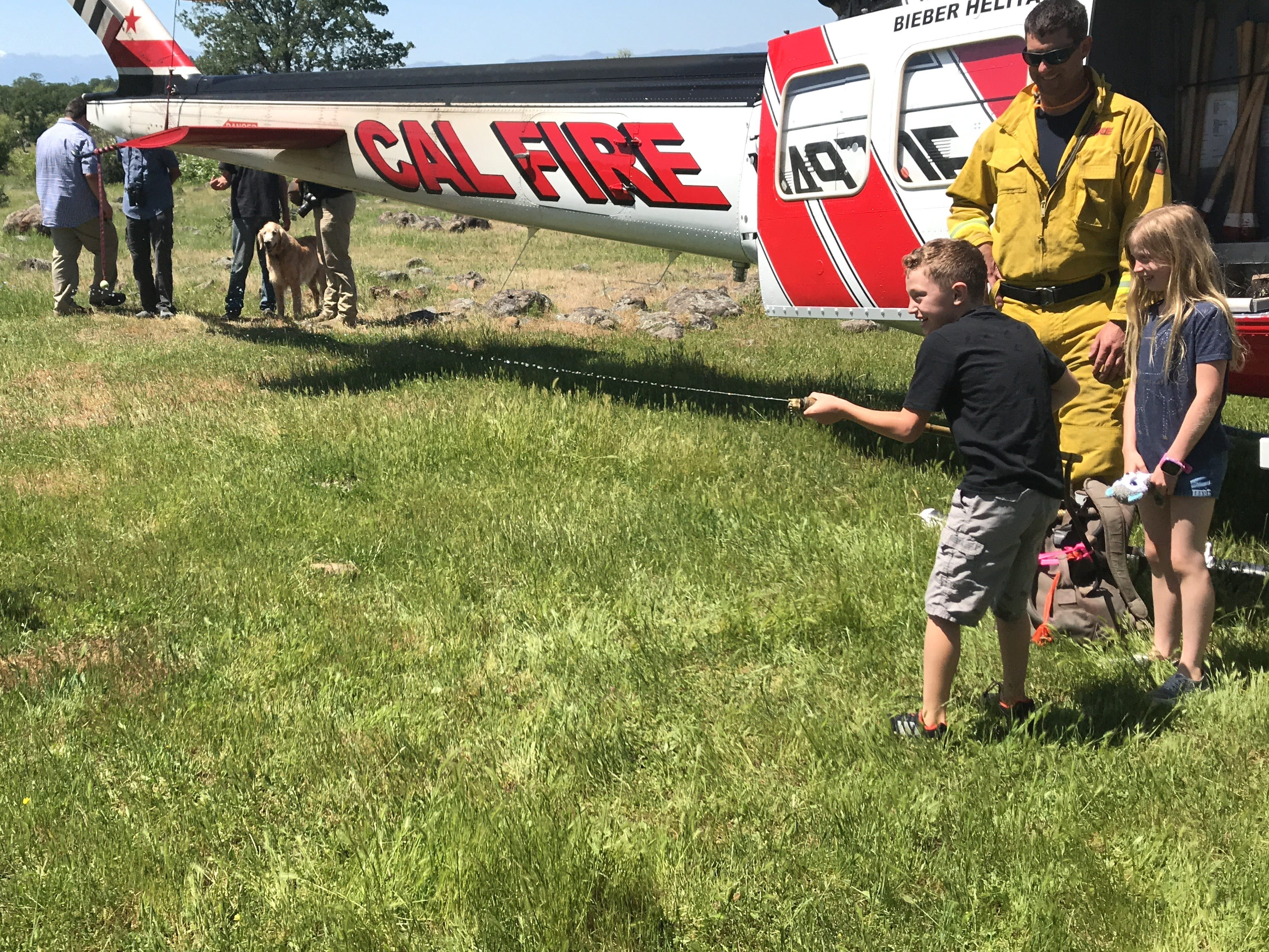 Children play with a water pack as the U.S. Forest Service and Cal Fire conducted aerial firefighting training in the skies above Whitmore on May 2, 2019.