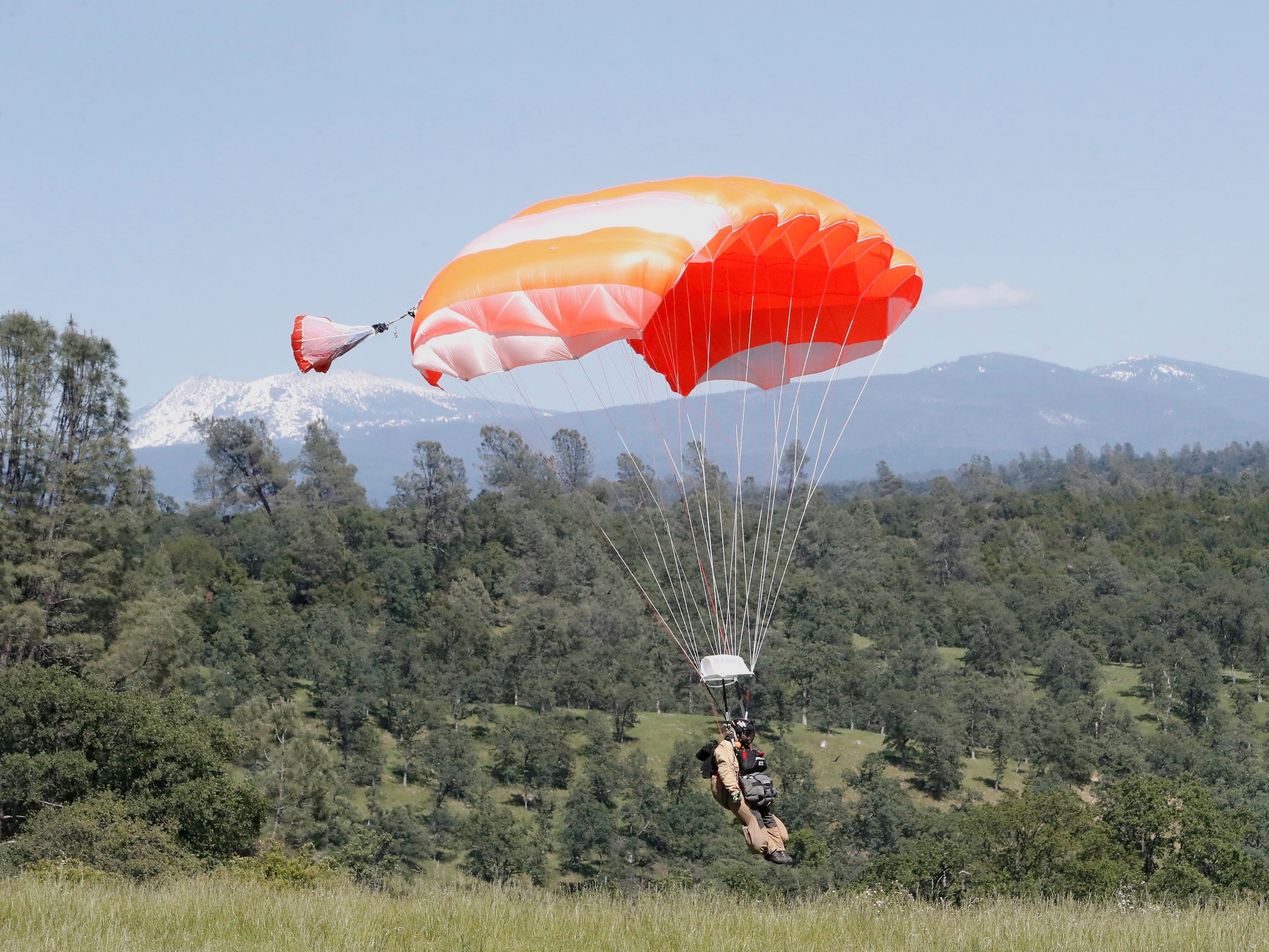 A smokejumper descends to earth during aerial firefighting training with Lassen Peak in the background.