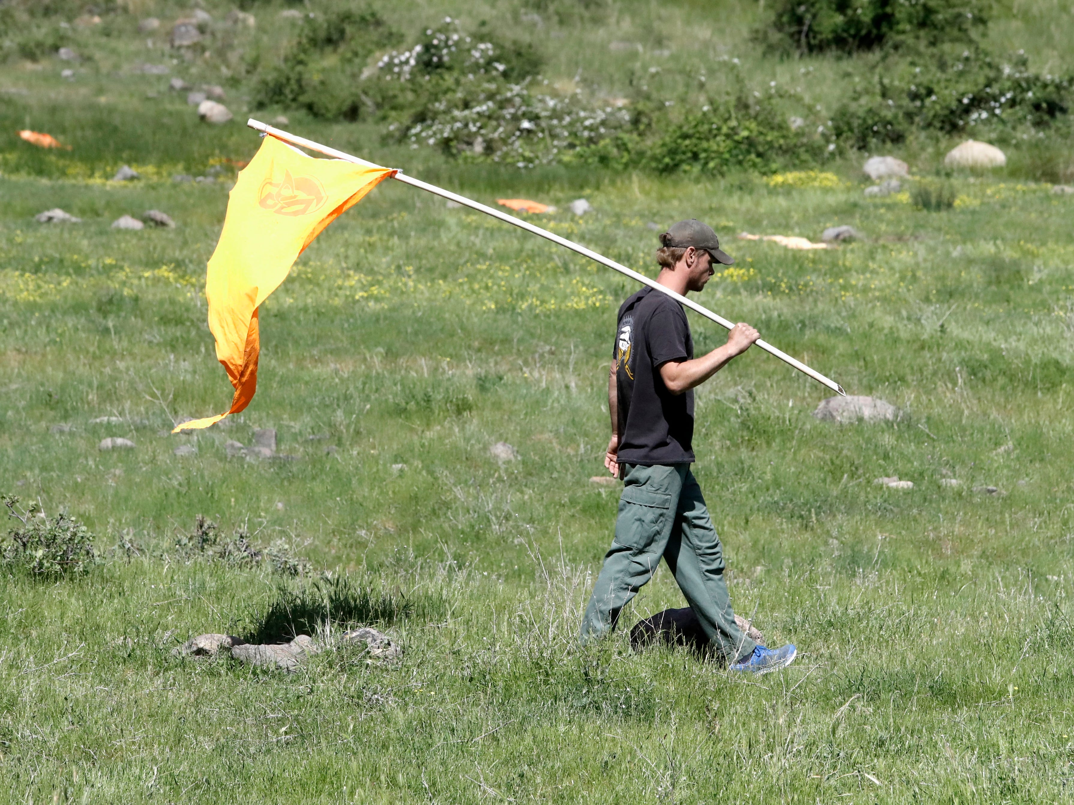 Planting a flag to gauge wind speed for a smokejumper landing.
