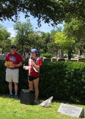 Girl Scout's Vivian Yale runs the flag holder placing event at Fairmount Cemetery 1120 W. Ave. N. Sunday, April 28, 2019.