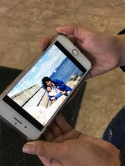 Missy Pham, the youngest student to graduate from O'Gorman High School in recent history, shows the photo she has saved on her phone of her mother Stephanie Pham, after her mother died unexpectedly in February.