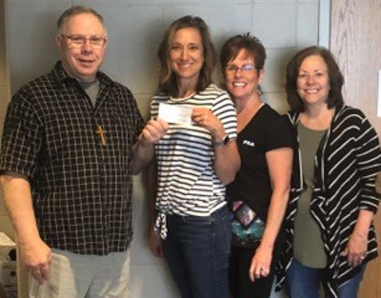 Pastor Jeff Sorenson accepts the DRAMA donation from Uncork and Unwind. Presenting the check are ESA members Lori Morris, Glenda Siemonsma and Diana Jones.
