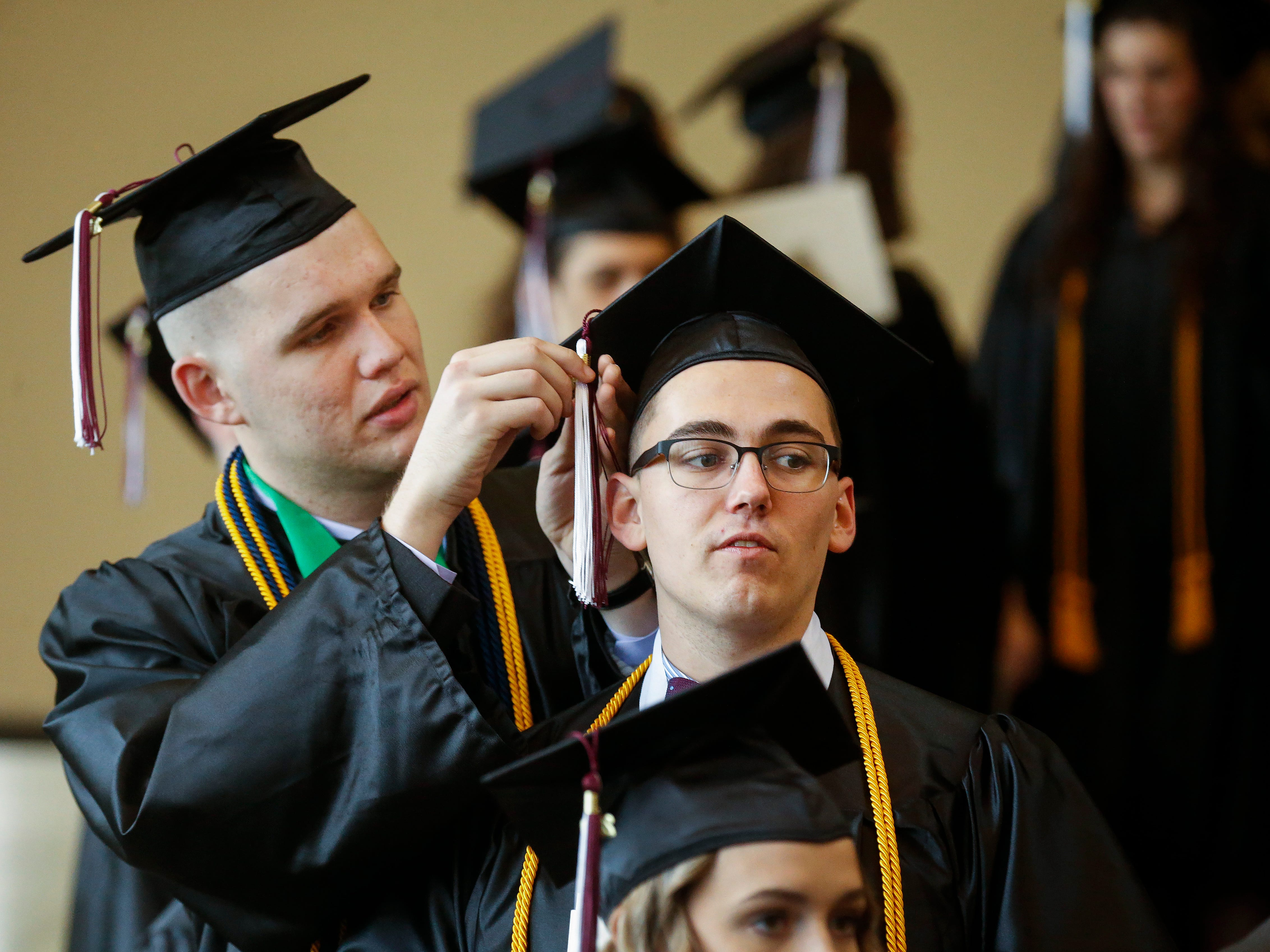 Kendall Mayo, left, fixes Evan Masters' tassel before Evangel University's 2019 Commencement Ceremony at James River Church in Ozark on Friday, May 3, 2019.