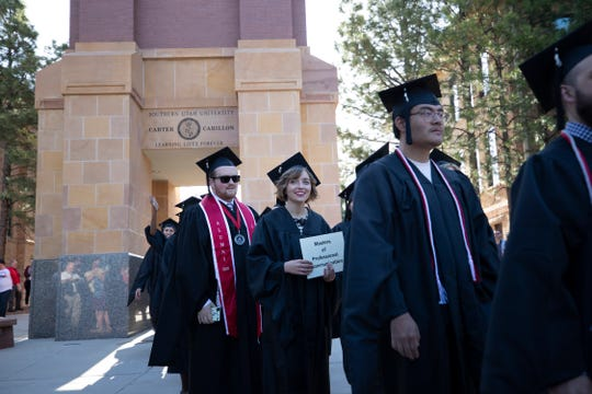 Graduates participate in the traditional procession beneath the belltower on their way to the commencement ceremony at Southern Utah University on Friday, May 3, 2019.
