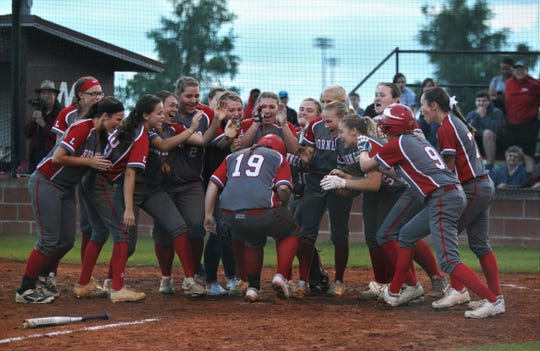 Lafayette's softball team greets Hannah Murray at home plate after she hit a solo home run in the fourth inning that prove to be the game-winning run in a 1-0 upset of Madison County during a District 5-1A championship on Thursday in Madison.