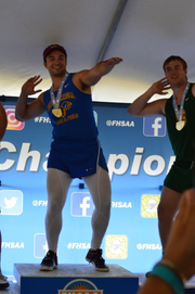 John Carroll Catholic senior thrower Jacob Hoeffner celebrates on the podium after winning the gold medal in the shot put on Friday at the University of North Florida in Jacksonville.