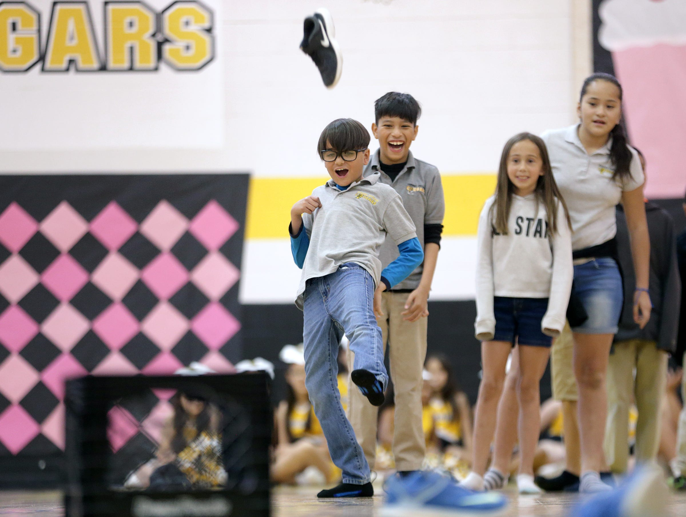 Hurshel Antwine Elementary students try to kick their shoes into a milk crate as they play a game at the school's STAAR rally Friday.