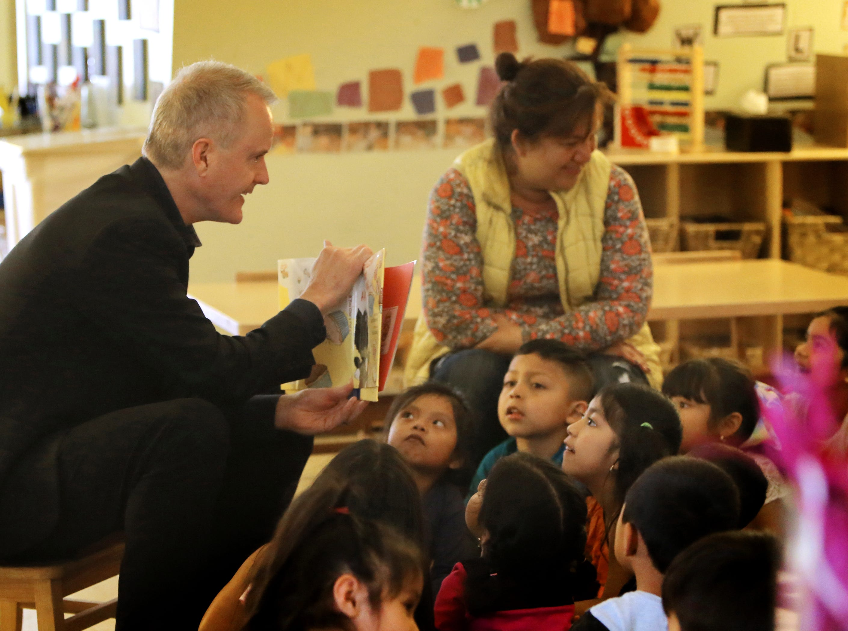 Children from La Escuelita Child Development Center in Oxnard listen to Ventura County Executive Officer Michael Powers read a book during the  Take 5 and Read to Kids campaign on Friday.