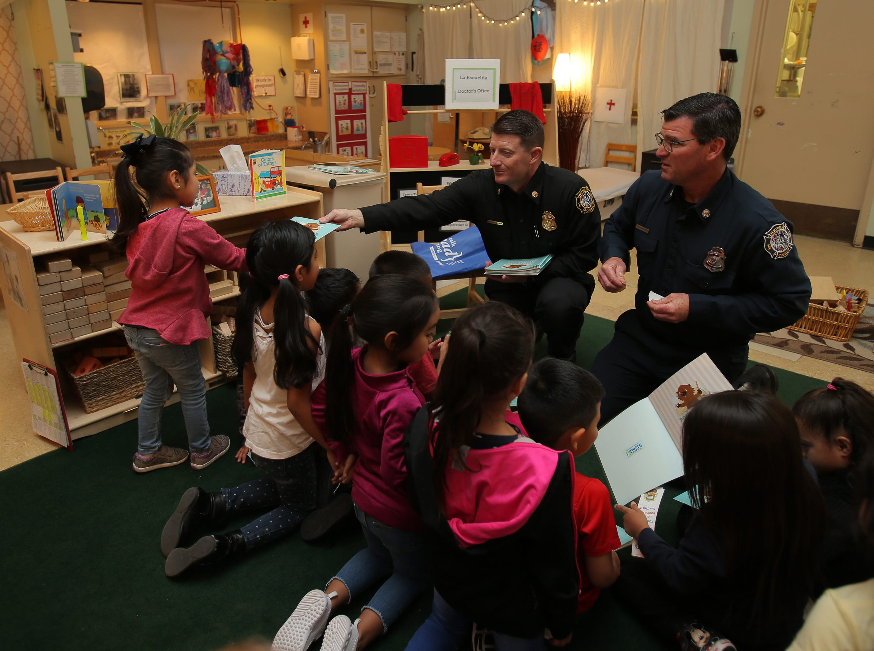Ventura County Fire Deputy Chief Dustin Gardner (left) and Public Information Officer Brian McGrath hand out books to preschoolers during the fourth annual Take 5 and Read to Kids campaign Friday at La Escuelita Child Development Center in Oxnard. The campaign is a partnership between  First 5 Ventura County and The Star to raise the awareness about the importance of early childhood literacy.