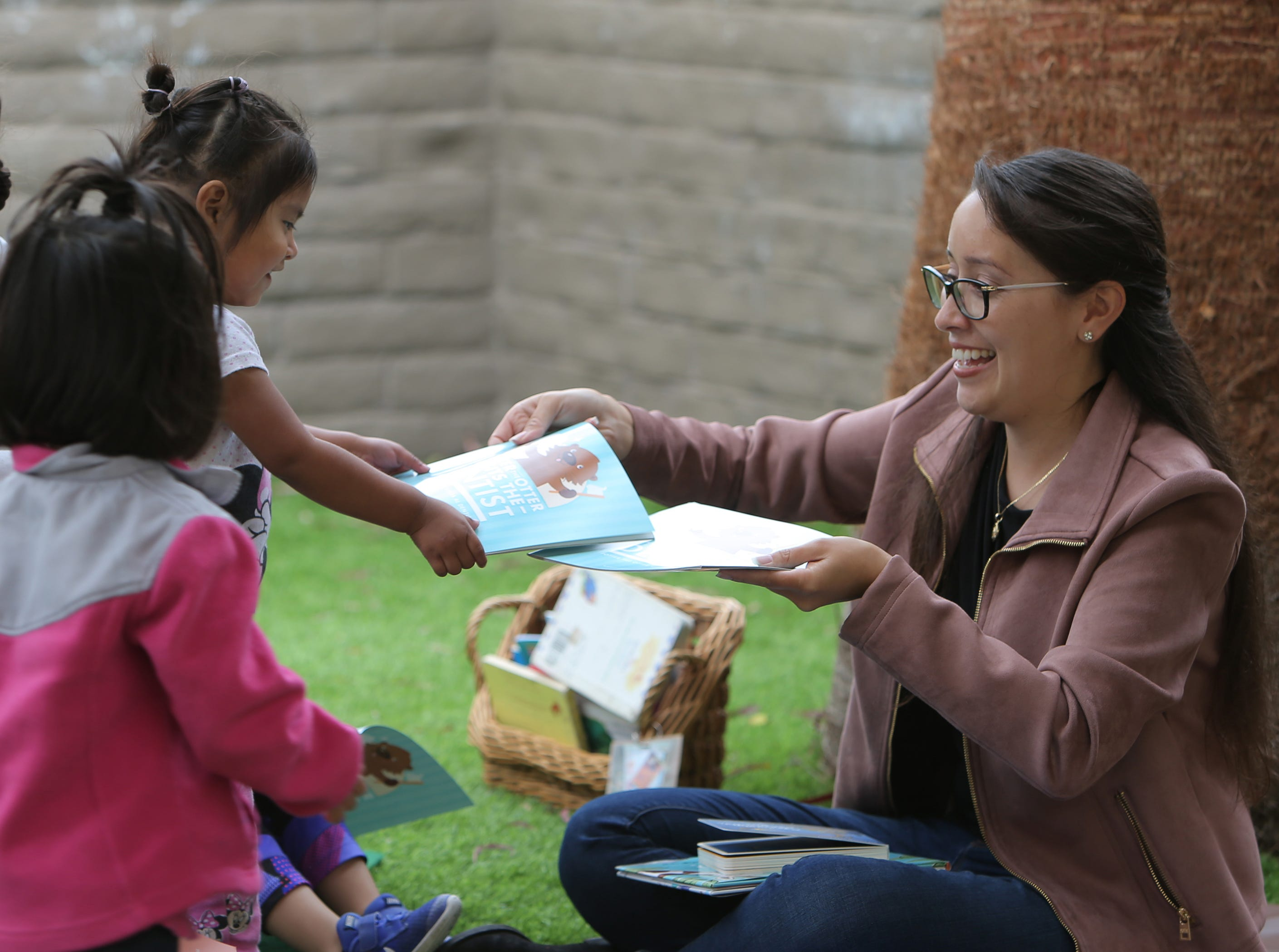 Yoana Lopez, 2, receives to book from Oxnard City Council member Vianey Lopez during the Take 5 and Read to Kids campaign Friday at La Escuelita Child Development Center in Oxnard.