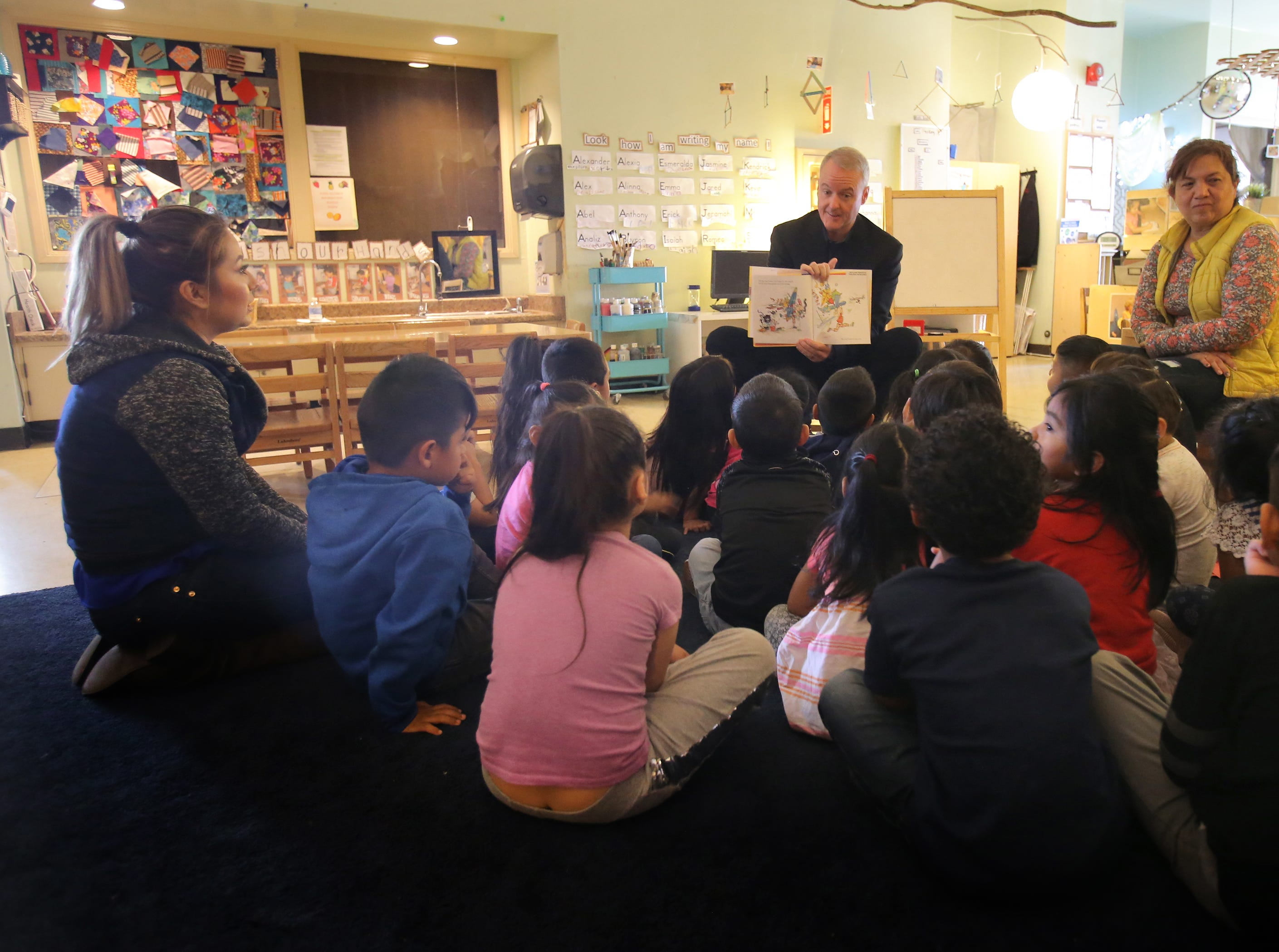 Children from La Escuelita Child Development Center in Oxnard listen as Ventura County Executive Officer Michael Powers reads a book during the Take 5 and Read to Kids campaign on Friday in Oxnard.