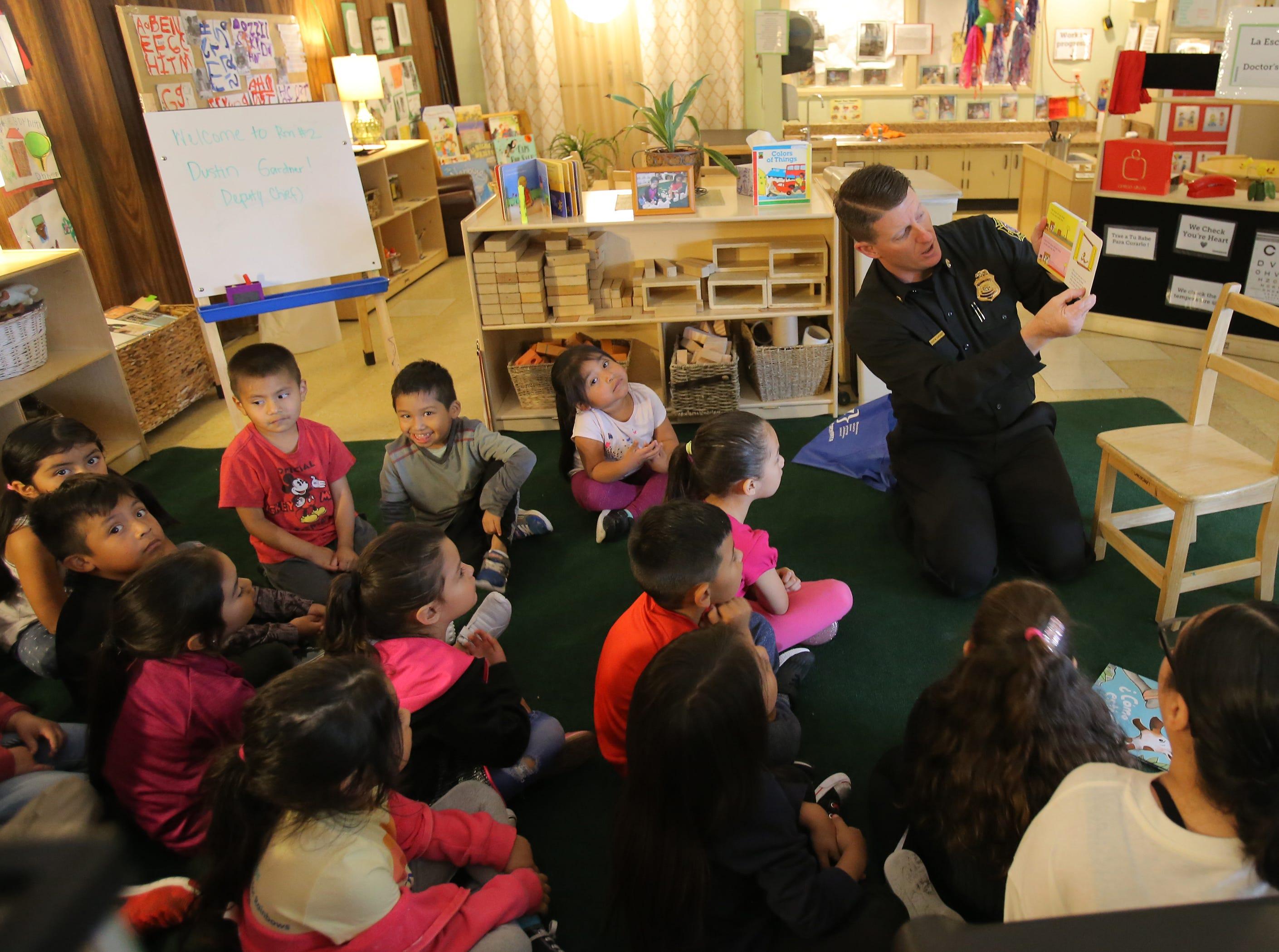 Ventura County Fire Deputy Chief Dustin Gardner reads to preschoolers during the fourth annual Take 5 and Read to Kids campaign at La Escuelita Child Development Center in Oxnard.