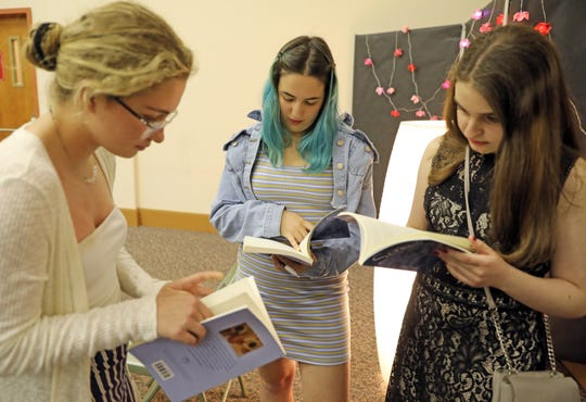From left, Ava Raffa of Pearl River High School, Hannah Hollender and Julia Jed both of Suffern High School look at their entry in the Scrawl book during the Scrawl book launch party at Pearl River Library May 2, 2019.