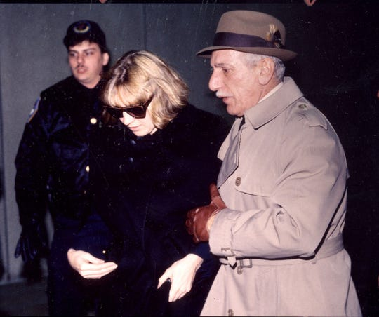 -  -Text: Carolyn Warmus leaves Westchester County Courthouse in White Plains escorted by body guard Mike DiSalvatore Jan. 3, 1991. Court officer in back ground is not identified.